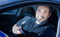 Homme d'affaires souriant dans la voiture Images stock