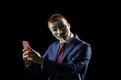 Homme d'affaires sous le déguisement de masque étant anonyme et impliquant qu'il est un pirate informatique ou un anarchiste Image libre de droits