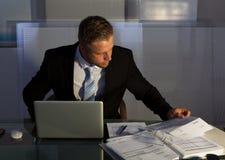 Homme d'affaires sous pression travaillant des heures supplémentaires Photos stock