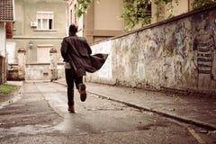 Homme d'affaires sprintant le long de la rue, vue arrière image stock