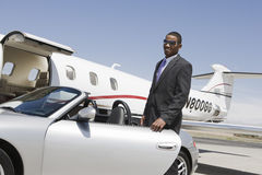 Homme d'affaires Standing By Car à l'aérodrome Photographie stock
