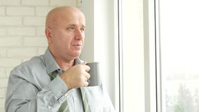 Homme d'affaires Stay sur le boire de fenêtre songeur une tasse de thé banque de vidéos