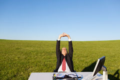Homme d'affaires Stretching At Desk sur le champ herbeux contre le ciel Images stock