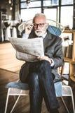Homme d'affaires supérieur à ses journaux d'équitation de bureau Photos libres de droits