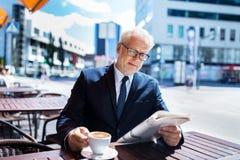 Homme d'affaires supérieur avec du café potable de journal Photographie stock