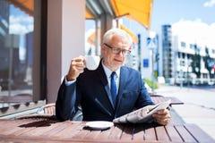 Homme d'affaires supérieur avec du café potable de journal Images libres de droits
