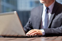 Homme d'affaires supérieur avec l'ordinateur portable au café extérieur Photos stock