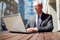 Homme d'affaires supérieur avec l'ordinateur portable au café extérieur Photos libres de droits