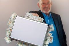 Homme d'affaires supérieur avec la serviette pleine des dollars Images stock