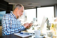 Homme d'affaires supérieur avec le smartphone et l'ordinateur portable en café Photographie stock libre de droits