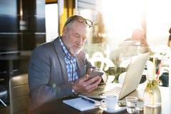 Homme d'affaires supérieur avec le smartphone et l'ordinateur portable en café Photographie stock