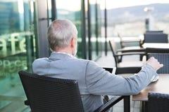 Homme d'affaires supérieur avec un comprimé en café de dessus de toit Photo libre de droits