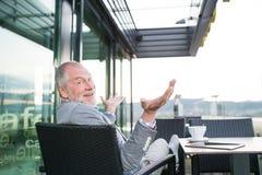 Homme d'affaires supérieur avec un comprimé en café de dessus de toit Photos libres de droits
