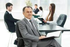Homme d'affaires supérieur avec un presse-papiers sur le fond du bureau Image libre de droits