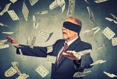 Homme d'affaires supérieur bandé les yeux essayant d'attraper des billets de banque de billets d'un dollar Photographie stock libre de droits
