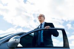 Homme d'affaires supérieur entrant dans la voiture Image stock