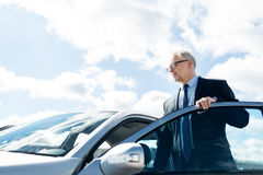 Homme d'affaires supérieur entrant dans la voiture Photo stock