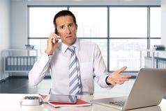 Homme d'affaires supérieur fâché dans l'effort fonctionnant et parlant au téléphone portable au bureau d'ordinateur Photos stock