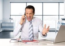 Homme d'affaires supérieur fâché dans l'effort fonctionnant et parlant au téléphone portable au bureau d'ordinateur Photos libres de droits