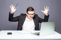 Homme d'affaires supérieur fâché s'asseyant à son bureau et criant Homme d'affaires fâché avec trop de travail dans le bureau You Photo libre de droits