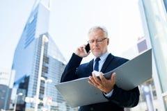 Homme d'affaires supérieur invitant le smartphone dans la ville Image libre de droits