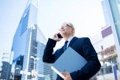 Homme d'affaires supérieur invitant le smartphone dans la ville Photographie stock libre de droits