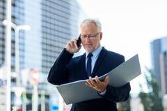 Homme d'affaires supérieur invitant le smartphone dans la ville Photos stock