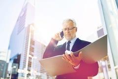 Homme d'affaires supérieur invitant le smartphone dans la ville Photo stock