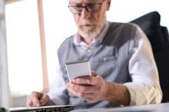 Homme d'affaires supérieur lisant un message à son téléphone portable, lumière dure image libre de droits