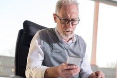 Homme d'affaires supérieur lisant un message à son téléphone portable, lumière dure photographie stock