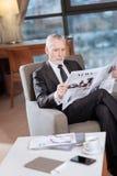 Homme d'affaires supérieur sérieux passant en revue des actualités Photographie stock
