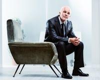 Homme d'affaires supérieur songeur s'asseyant dans un fauteuil Image stock