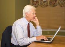 Homme d'affaires supérieur sur l'ordinateur portable photos stock