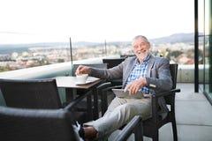 Homme d'affaires supérieur travaillant au comprimé en café de dessus de toit Image libre de droits
