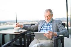 Homme d'affaires supérieur travaillant au comprimé en café de dessus de toit Photographie stock