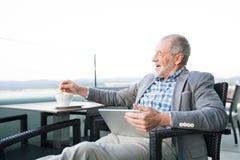 Homme d'affaires supérieur travaillant au comprimé en café de dessus de toit Images libres de droits