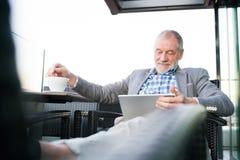 Homme d'affaires supérieur travaillant au comprimé en café de dessus de toit Photo libre de droits