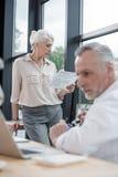 Homme d'affaires supérieur travaillant sur l'ordinateur portable avec le collègue féminin Image stock