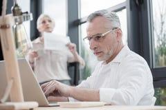 Homme d'affaires supérieur travaillant sur l'ordinateur portable avec le collègue féminin Photo libre de droits