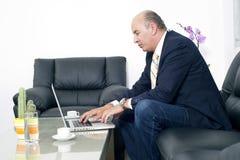 Homme d'affaires supérieur travaillant sur l'ordinateur portable dans son bureau Photos libres de droits