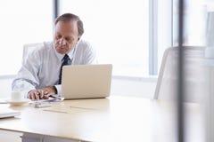 Homme d'affaires supérieur Working On Laptop au Tableau de salle de réunion Photographie stock libre de droits