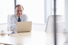 Homme d'affaires supérieur Working On Laptop au Tableau de salle de réunion Photos stock