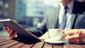 Homme d'affaires sup?rieur avec le PC et le caf? de comprim? image stock