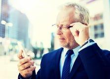Homme d'affaires sup?rieur avec le smartphone dans la ville photos stock