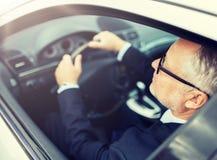 Homme d'affaires sup?rieur heureux conduisant la voiture photographie stock