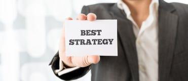 Homme d'affaires supportant une carte indiquant la meilleure stratégie Images stock