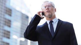 Homme d'affaires supérieur invitant le smartphone dans la ville banque de vidéos