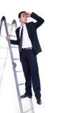 Homme d'affaires sur l'échelle recherchant des possibilités Photo stock
