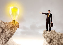 Homme d'affaires sur la montagne de roche avec l'ampoule d'idée Images stock