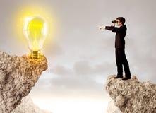 Homme d'affaires sur la montagne de roche avec l'ampoule d'idée Photos libres de droits
